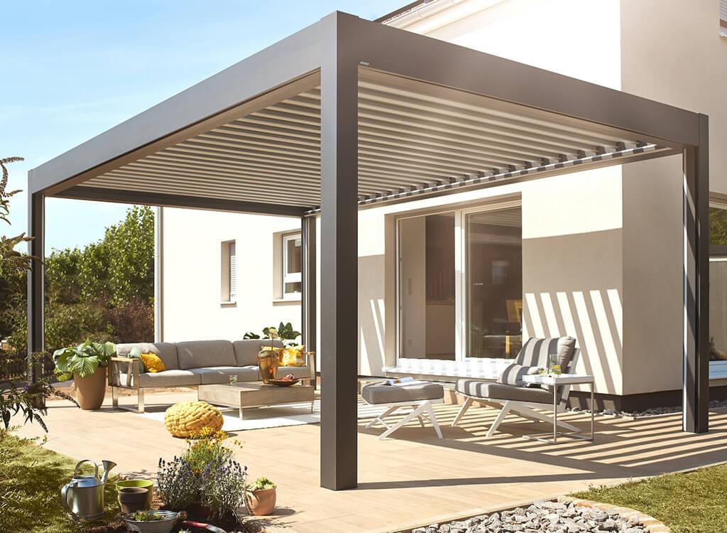 Lamellendach-als-Ueberdachung-fuer-eine-Aussen-Terrasse-mit-Sitzmoeglichkeiten-an-einem-modernen-Haus
