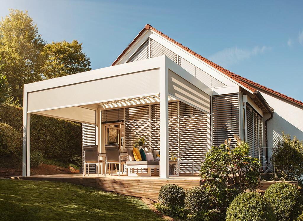 graues-Lamellendach-als-Ueberdachung-fuer-eine-Aussen-Terrasse-mit-Sitzmoeglichkeiten-an-einem-weissen-Haus